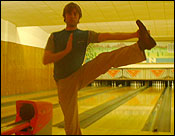 Noel doing a yoga pose after bowling a strike.