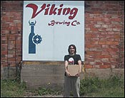 Me outside by the Viking Brewery sign with my case of beer that I bought.